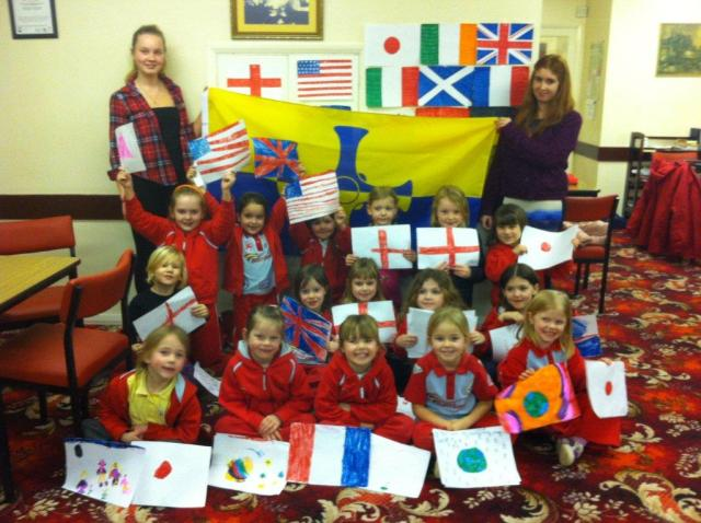 2nd Meadowfield Rainbows and their flags in front of the County Durham flag